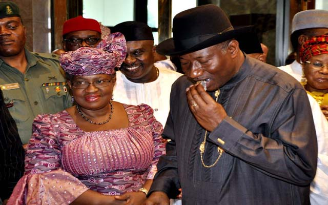 PRESIDENT GOODLUCK JONATHAN TAKING A BITE FROM THE CAKE PRODUCED FROM THE BENEFICARY OF YOU -WIN PROJECT  WHILE CORDINATOR OF THE NATIONAL ECONOMIC TEAM AND MINISTER OF FINANCE, DR, NGOZI OKONJO -IWEALA LOOKS ON AT THE PRESENTATION CEREMONY OF YOU-WIN PRODUCTS  HELD AT THE PRESIDENTIAL VILLA ,ABUJA ..YESTERDAY (03-07-2013) . GODWIN OMOIGUI